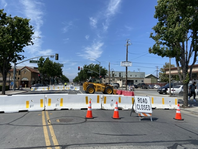 Tractors placing additional red barriers to block off driveways and business fronts at South and San Benito Streets. Photo by Patty Lopez Day.