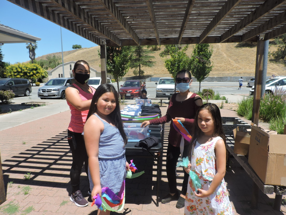 Nelcy Pulido Cruz (left), her daughter Ruby Pulido(center left), neice Clara Elena (center right) and sister Esperanza Cruz (back right) pick up supplies to decorate their cars to join the census caravan. Photos by Patty Lopez Day.