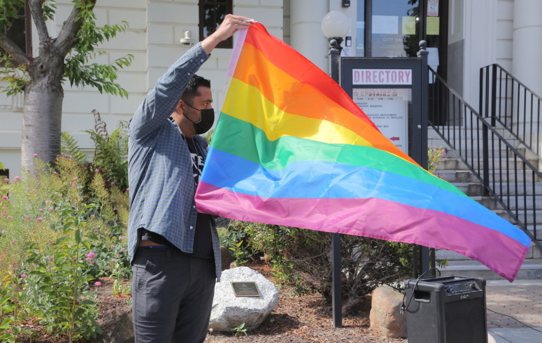 Raymond Anthony Andrade getting ready to raise the LGBTQ flag at City Hall in 2020. Photo by Robert Eliason.