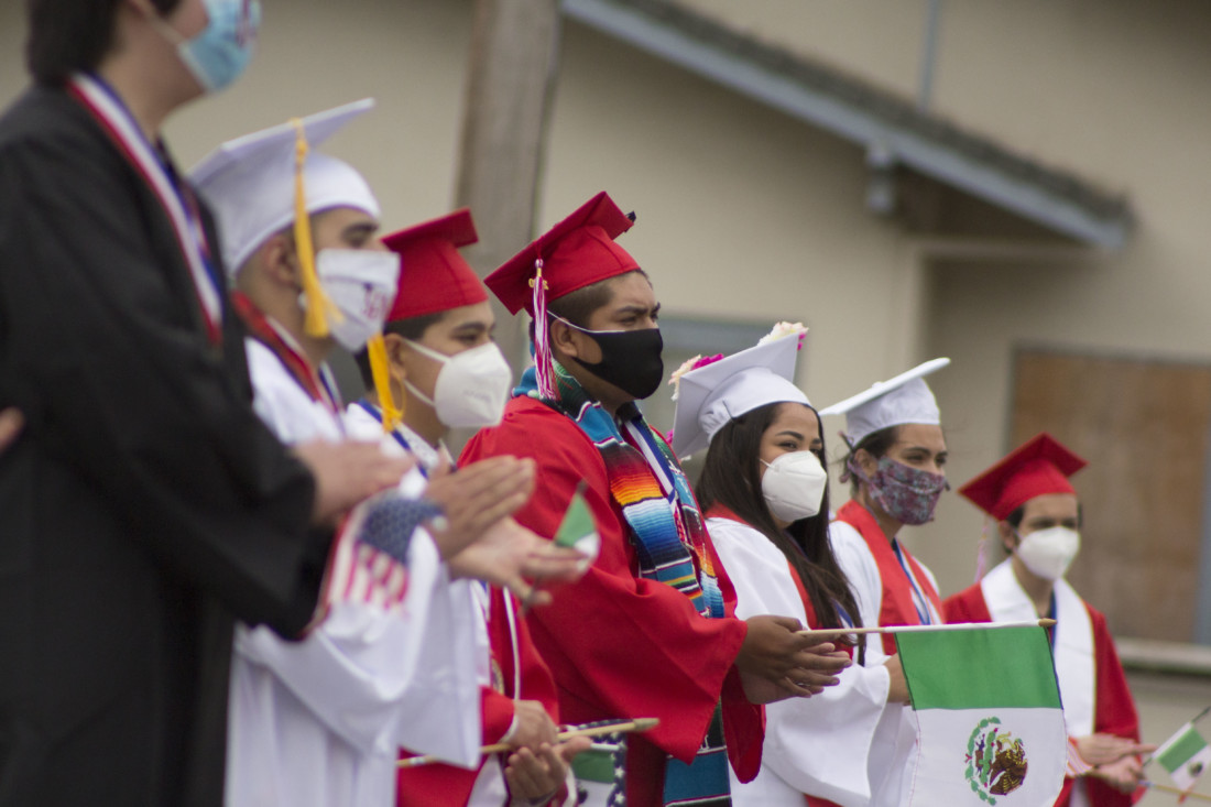 David Gonzalez (middle) joins other graduates in applauding during the ceremony. Photo by Noe Magaña.