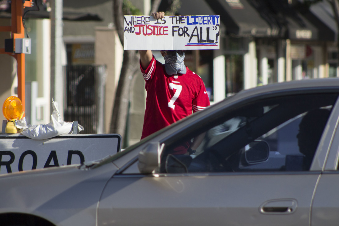Max Beltran lifts his sign for passing motorists on Fourth and San Benito streets in Hollister. Beltran and about 30 others took part in a June 5 demonstration to show support for the Black Lives Matter movement. Photos by Noe Magaña.