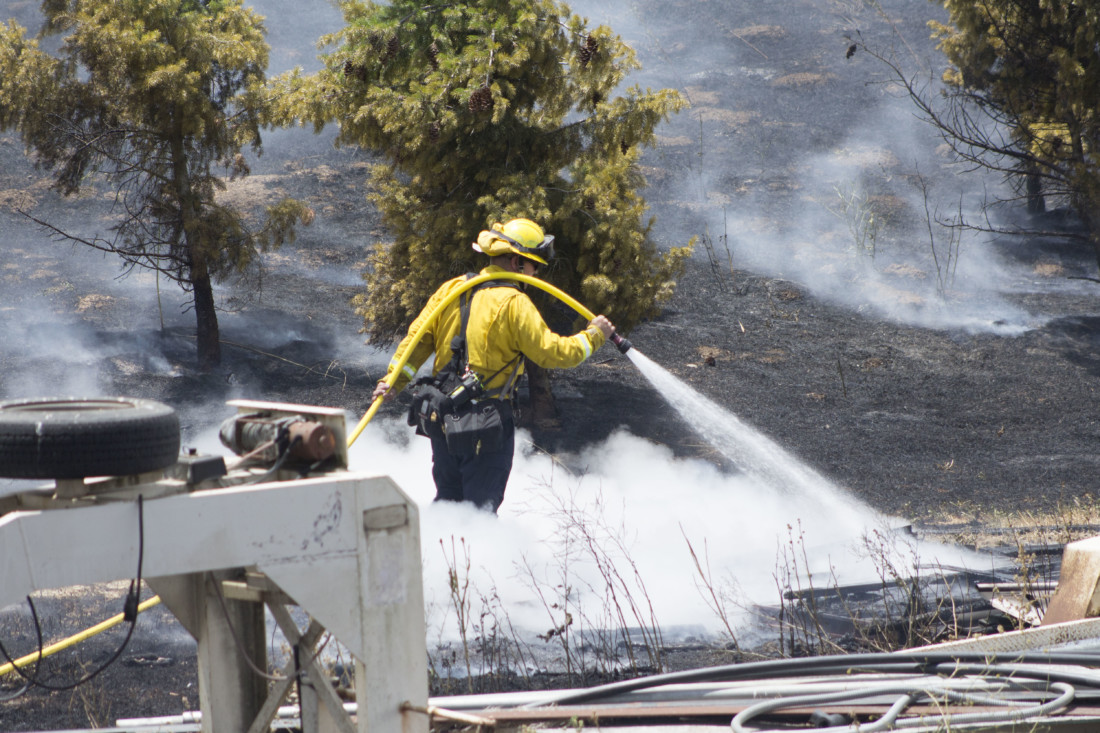 A Hollister firefighter works to contain a brush fire at Park Hill in Hollister on June 12. Photo by Noe Magaña.