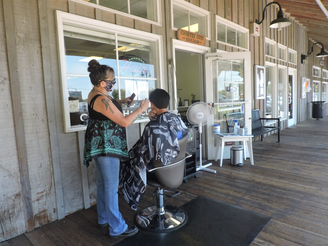 Stylist Cindy Gilroy cuts hair outside of the salon Country Cuts in San Juan Bautista. Photo by Patty Lopez Day.