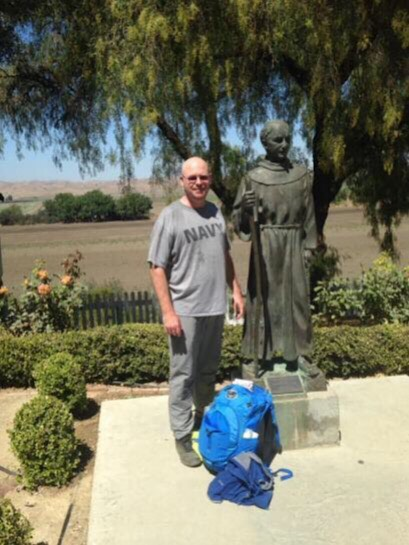 Clifford standing next to the statue of Saint Junípero Serra upon his arrival to Mission San Juan Bautista. Photo courtesy of Christian Clifford.