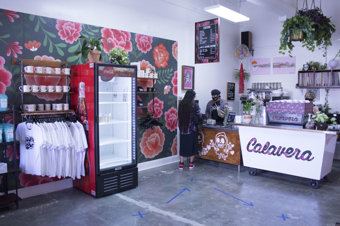 A flower mural adorns the wall near all the coffee cups, shirts and other merchandize. Photo by Noe Magaña.
