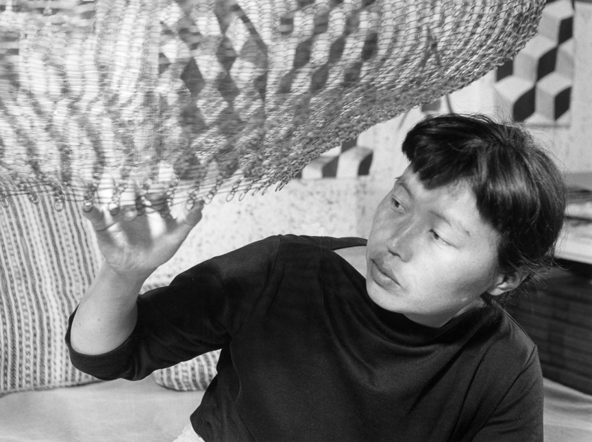 Artist Ruth Asawa creating a looped wire structure (circa 1957). Photo courtesy of Akira Boch.