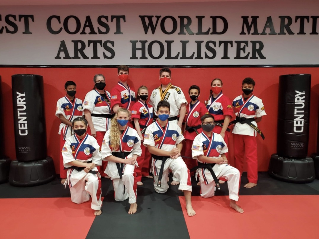 West Cost Hollister black belt testers. Standing: Zander Brister, Pamela Brister, Noah Fort, Lisa Fort, Nathan Fort, Aidan Fort, Julia Hicks, Miles Gamble. Kneeling: Ashley Cisneros-Avila, Sadel LoCascio, Jarrod LaFavre, Kyle Salazar. Photo courtesy of Nathan Fort.