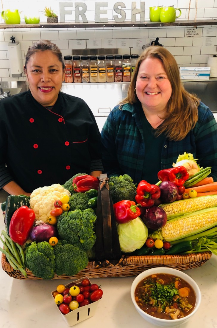 Luz Lopez and Soup for Seniors co-founder Becky Herbert display soup ingredients.