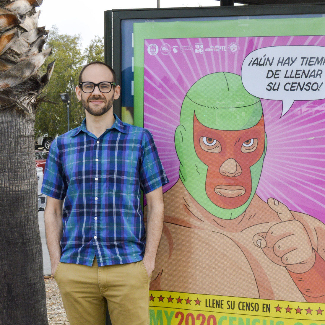 Artist Bryan West standing by poster he designed for the 2020 Census. Photo courtesy of Bryan West.