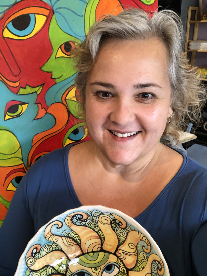 Cindy Couling poses with acrylic painting and ceramic bowl. Photo courtesy of Cindy Couling.