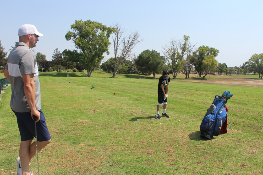 Hollister resident Neil Garrett swings at the golf range with son Cade. Photo by Julia Hicks.