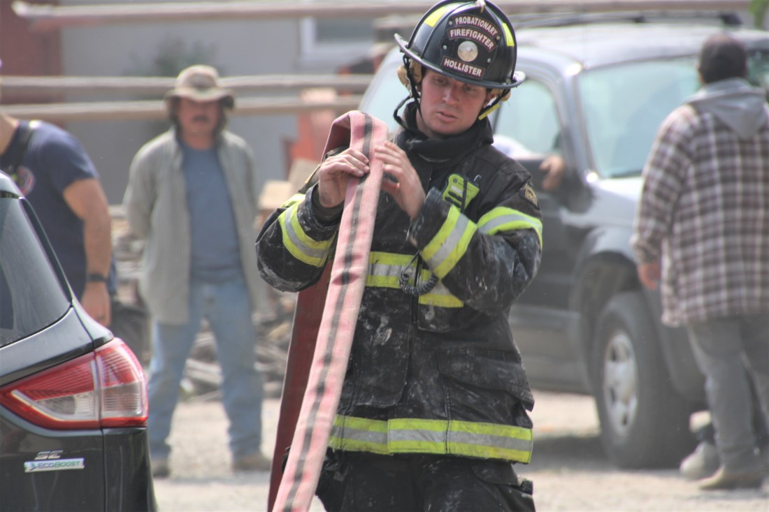 A Hollister firefighter rolls up hoses after a structure fire at 2561 Fallon Road on Sept. 14. Photo by John Chadwell.