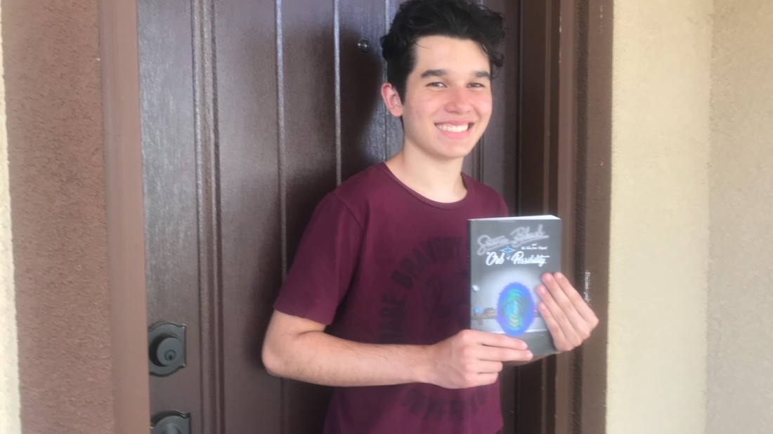 James Owen Welch holding a copy of debut book, 'Steven Black and the Tales from Beyond: The Orb of Possibility.' Photo courtesy of Ryan Welch.