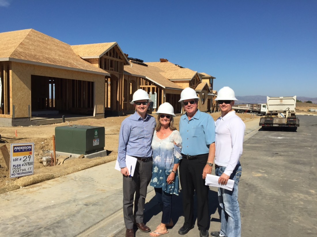 Michael, Georgeann, Larry and James Anderson stand in front of one of their housing projects. Photo provided by Anderson Homes
