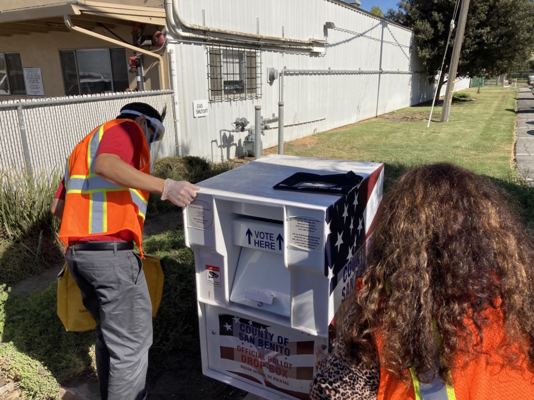 Dane Sanchez and Melinda Cortez inspecting the drop box for any signs of vandalism before collecting ballots. Photo by Noe Magaña.