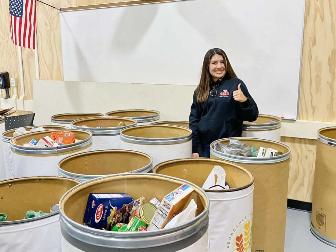 Baler Community Service Program founder Faith Fernandez next to the 12 barrels of nonperishable food collected by a recent canned food drive. Photo courtesy of Faith Fernandez.