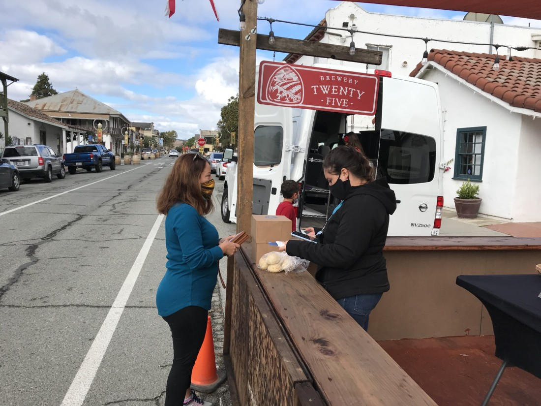 San Juan resident Andrea Balestrieri purchases her weekly order of sourdough cinnamon rolls from Black Pot Artisans owner Leslie Dell. Photo by Frank Perez.