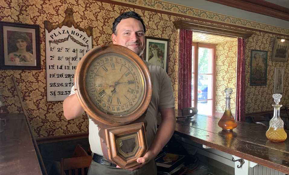San Juan Bautista State Historic Park interpreter Marcos Vizcaino in the Plaza Hotel Saloon with an antique clock. Photo by Robert Eliason.