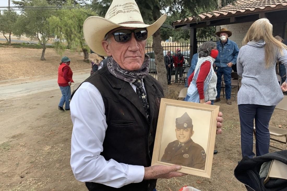 Joe Cousins with his father John's portrait. Photo by Robert Eliason.