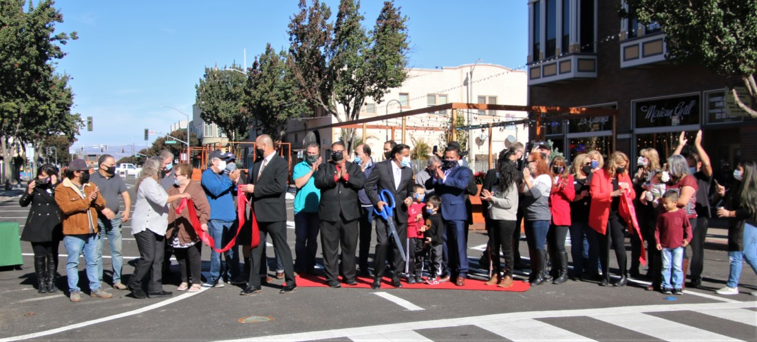 Elected officials and business owners line up for the ribbon-cutting ceremony. Photo by John Chadwell.