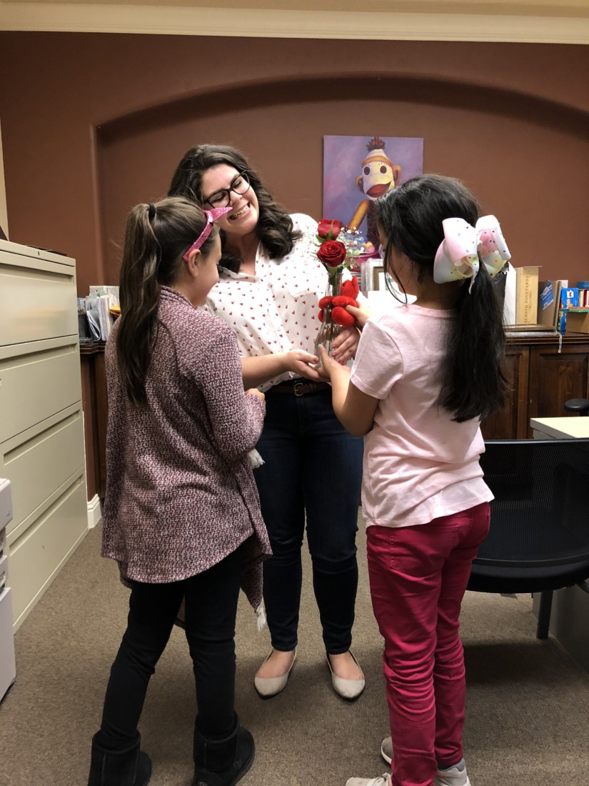 CASA staff and advocate Lori Arnold receiving a Valentine's Day gift from her CASA children. Photo courtesy of CASA.