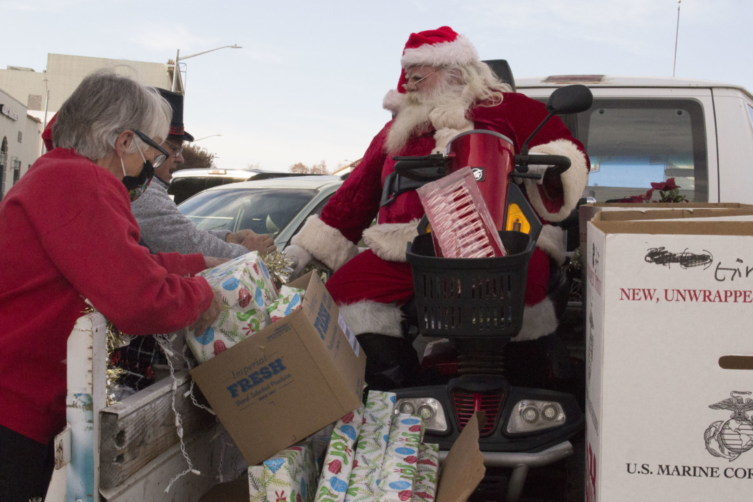 Linda Lampe and volunteers help load a truck and a trailer with toys next to Santa Claus to be delivered on Dec. 24. Photo by Noe Magaña.