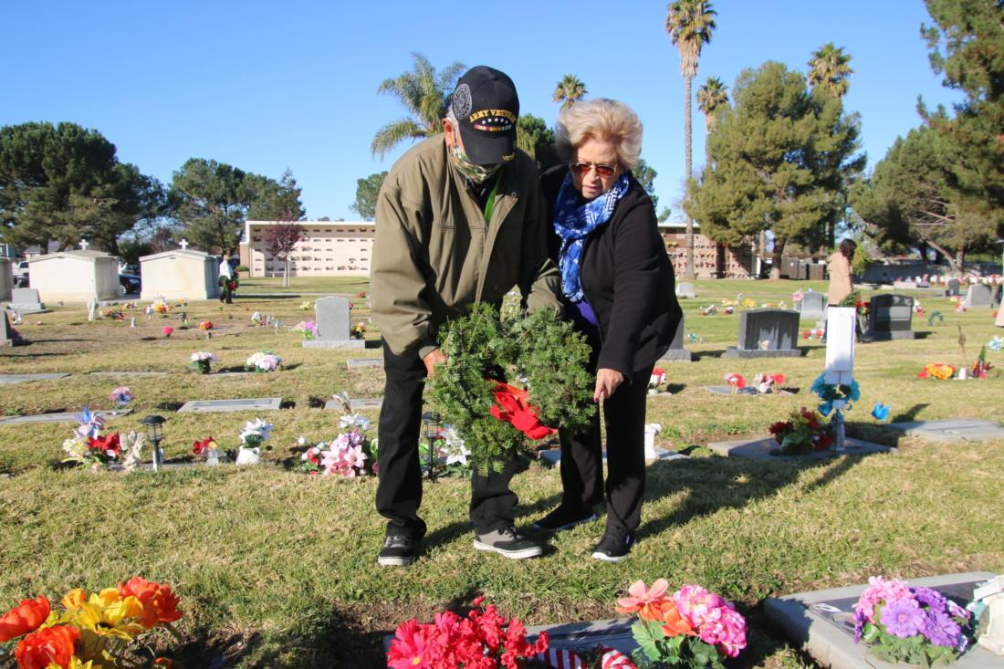 Mickie Luna and her husband Vince lay wreath at her brother's grave. Photo by John Chadwell.