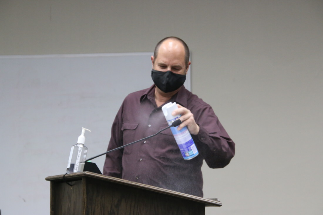 City Manager Brett Miller sprayed the podium with disinfectant between speakers. Photo by John Chadwell.
