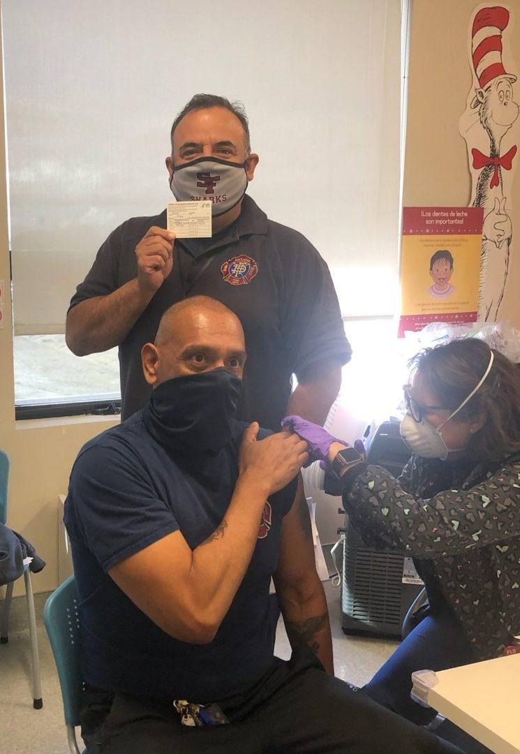 Fire Chief Bob Martin Del Campo receiving his COVID-19 vaccination. Charlie Bedolla is in the background. Photo courtesy of Hollister Fire Department.