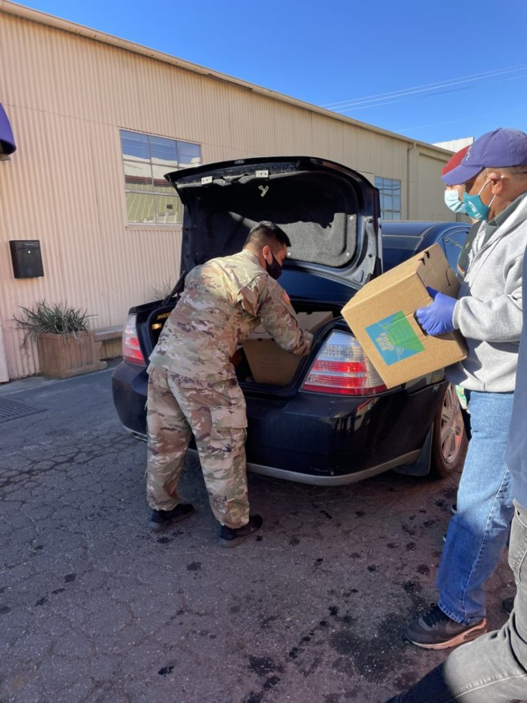 A National Guard sergeant and other volunteers load food into a trunk. Photo courtesy of Sarah Nordwick.
