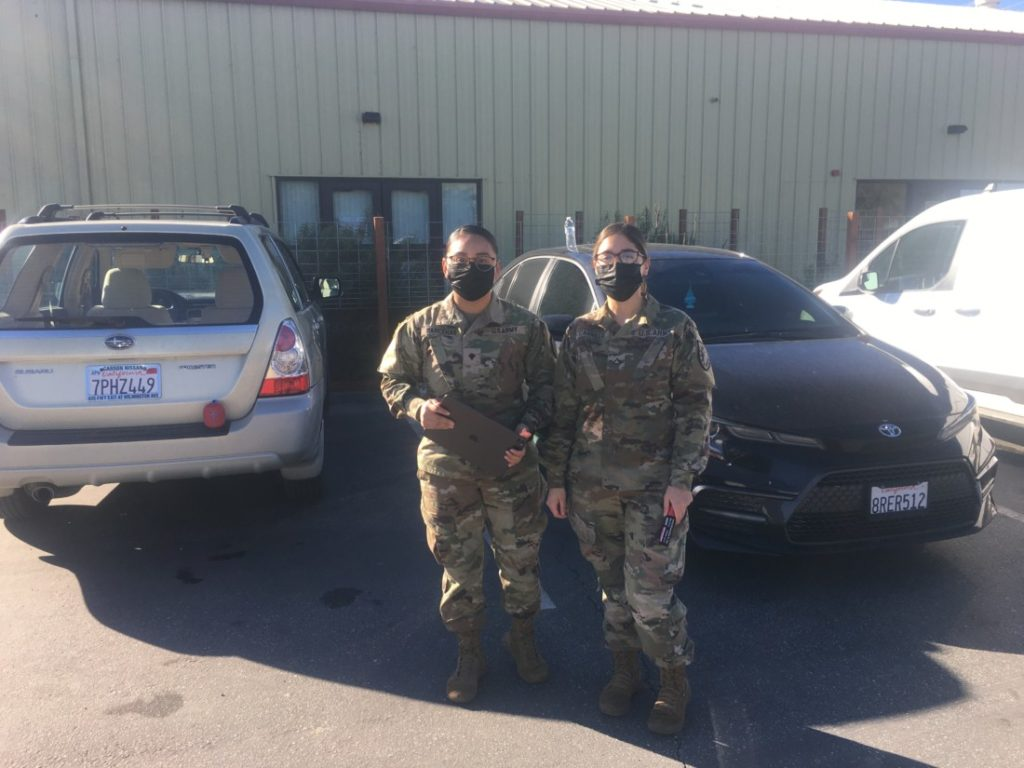 Pvt. Cynthia Barcenas and Pvt. Isabel Carrillo with the National Guard label each car at the food bank with the number of bags it should receive. Photo by Andrew Pearson.