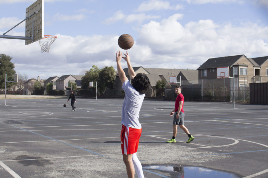 Izia Polanco, 19, and Kristian Espinoza, 20, playing basketball at Rancho San Justo Middle School. The basketball courts were typically used as the P.E area before the Hollister School District switched to distance learning. Photo by Noe Magaña.