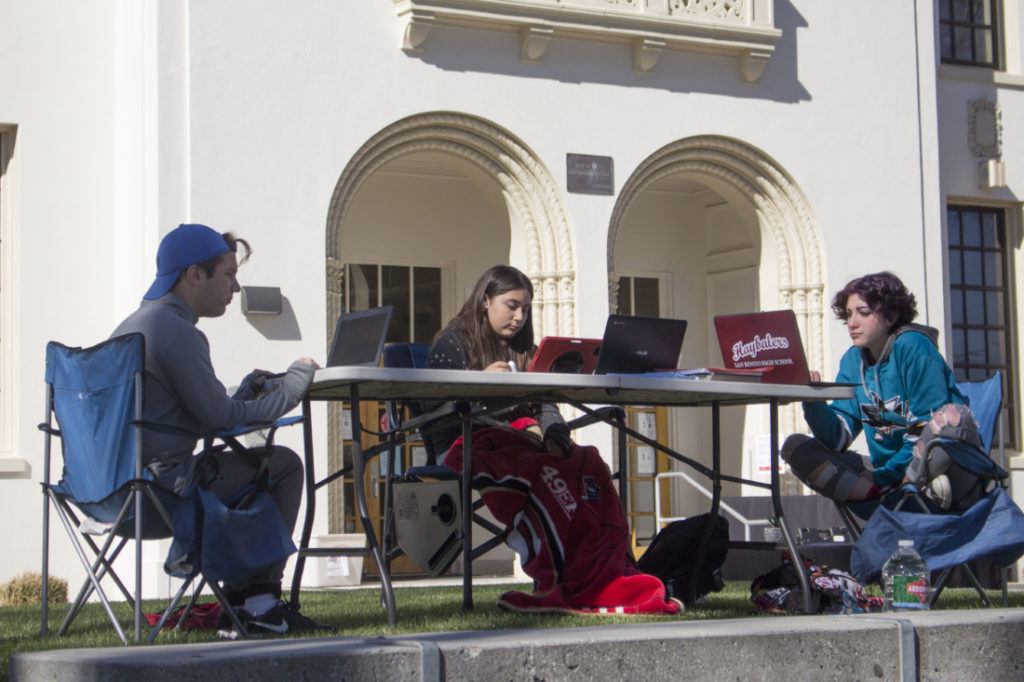 Conner Ortez, Sharon Bocanegra and Peyton Evans focus on their school work on a sunny morning. Photo by Noe Magaña.