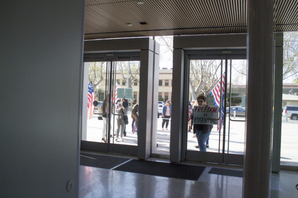A supporter peering through the doors of the courthouse while waiting for the hearing. Photo by Noe Magaña.