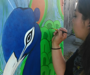 Hollister artist Danae Parra painting for the 2017 Utility Box Mural Project. Photo courtesy of SBC Arts Council.