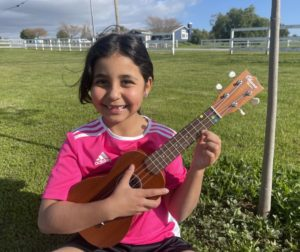 Ukulele student Sydney Luna poses with school instrument. Photo by Dreia Luna.