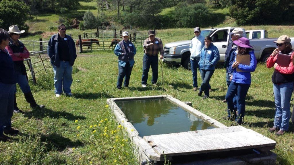 Joe Spencer explaining wildlife-friendly livestock trough design at ranch tour. Photo courtesy of Karminder Brown.