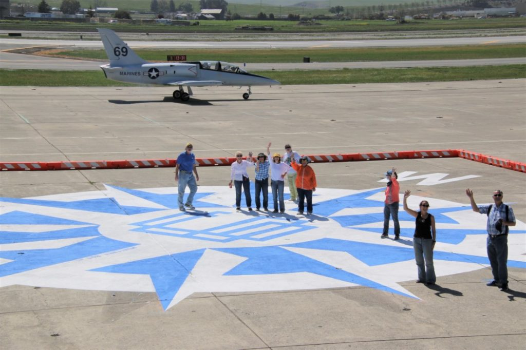 About 15 volunteers helped out for two days to paint the compass rose at the Hollister Municipal Airport. Photo by John Chadwell.