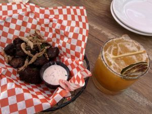 Gluten-free (coffee rubbed) Steak Bites, served with crispy shallots, along with a (locally sourced) B&R Apricot Margarita. Photo provided by Jenny Mendolla Arbizu.