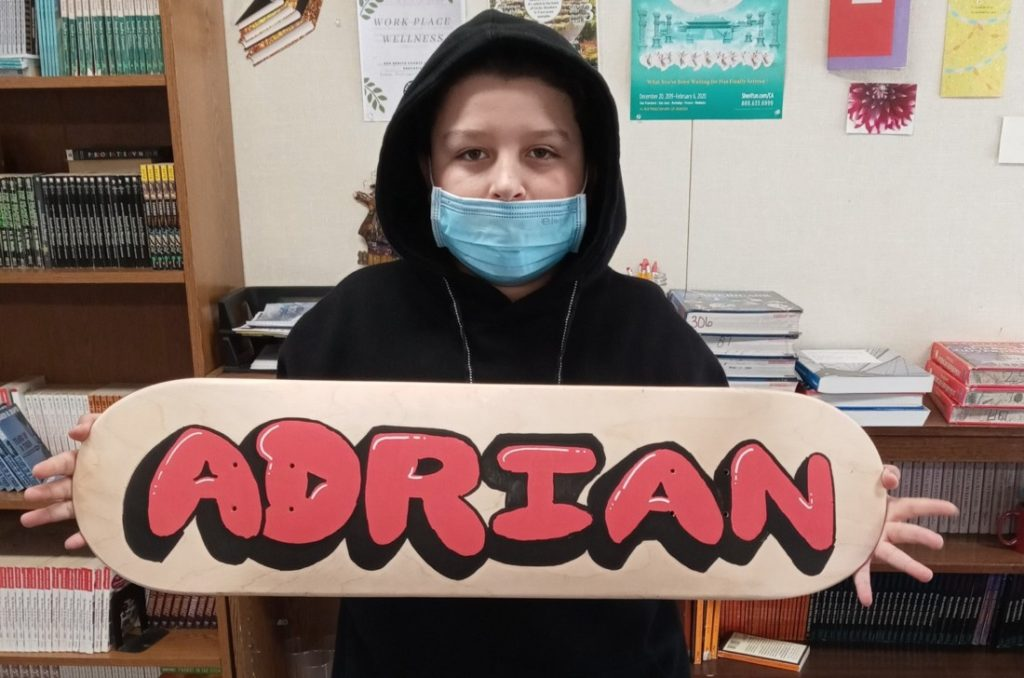 Adrian Avila, 8th grader at Santa Opportunity School, with his skateboard lettering project. Photo courtesy of Heidi Jumper.
