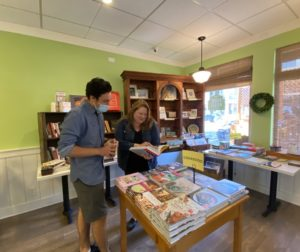 Farmhouse Cafe owner, Becky Herbert, assists customer in the cafe's new retail section of books. Photo by Jenny Mendolla Arbizu.