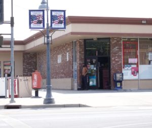 A shirtless resident shelters from the sun under the Pacheco's Liquors and Mart on June 16. Photo by Noe Magaña.