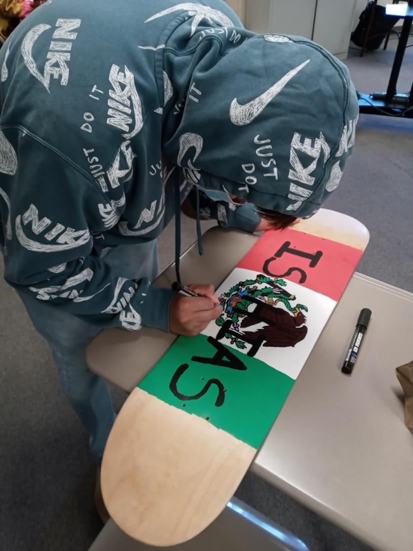 Isahias Perez-Ruiz, 8th grader at Santa Ana Opportunity School, with his skateboard project. Photo courtesy of Heidi Jumper.