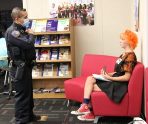 Hollister police officer talks with SBHS student Peyton Evans. She told him she could not wear a mask for medical reasons. He told her she had to leave building. Photo by John Chadwell.
