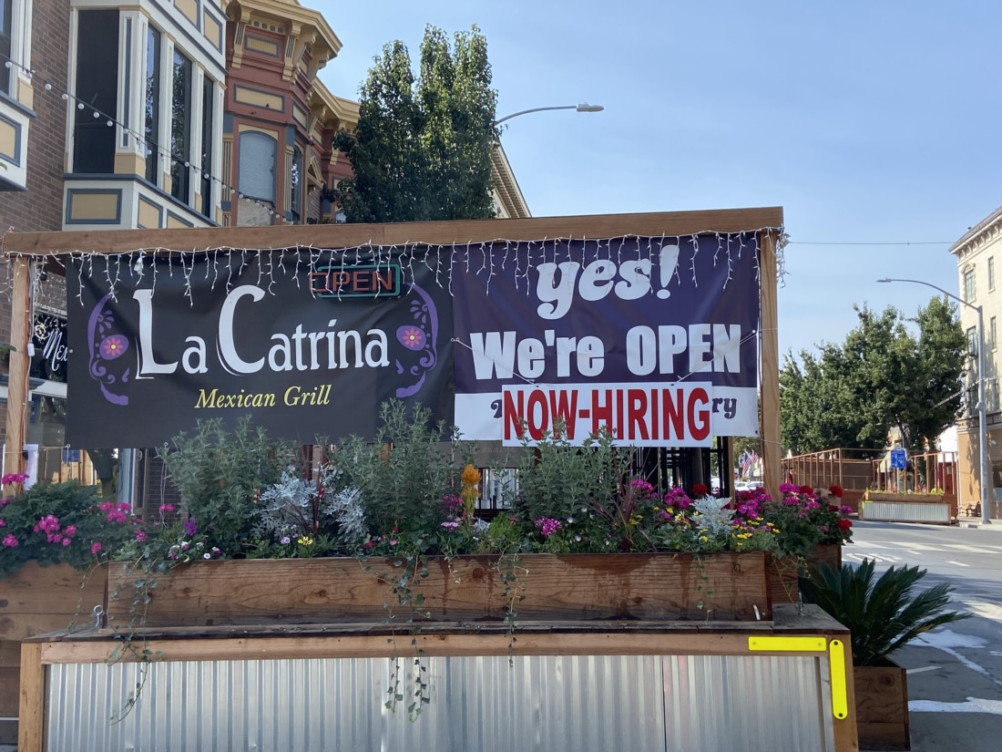 La Catrina's, at 449 San Benito Street, recently added 'Now Hiring' to its We're Open sign. Photo by Jenny Mendolla Arbizu.