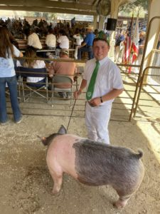 Tyler Abercrombie and Decimal the pig. Photo by Robert Eliason.