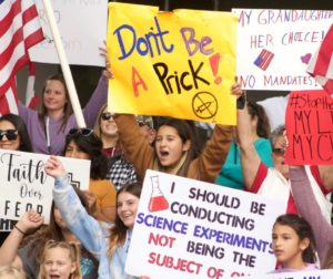 Protesters show their signs during a group photo during the Oct. 18 protest. Photo by Noe Magaña.
